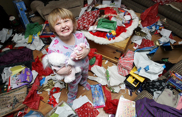 Kid surrounded by lots of presents